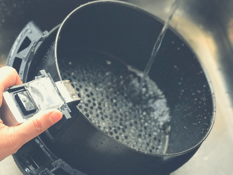 Rinsing an air fryer with tap water