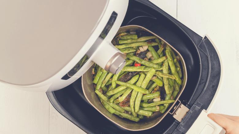 Green Beans air frying in an air fryer
