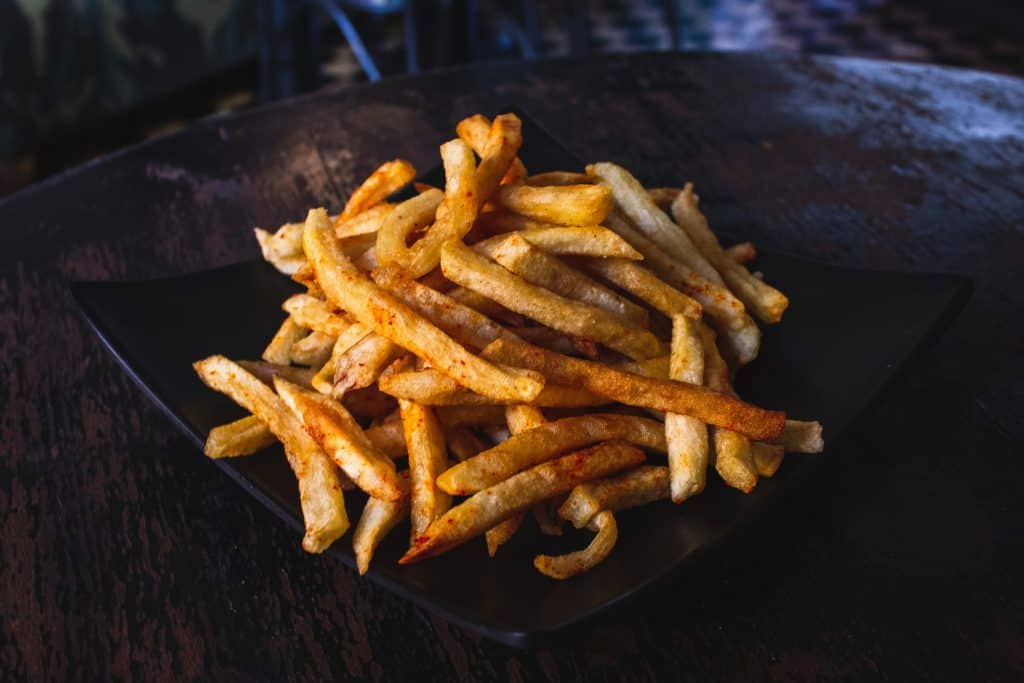Golden French fries from the air fryer, sprinkled with sweet paprika.