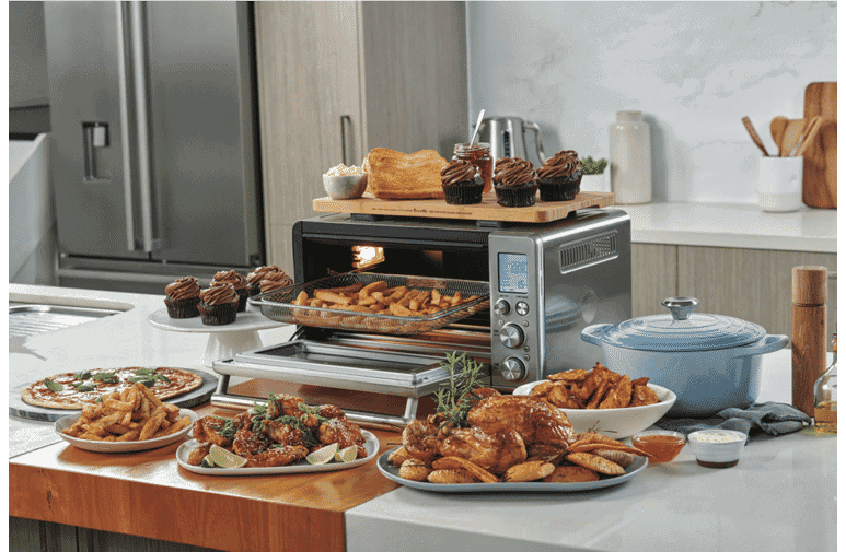 Convection oven-style air fryer with plates of air fried food and lots of air fryer accessories.